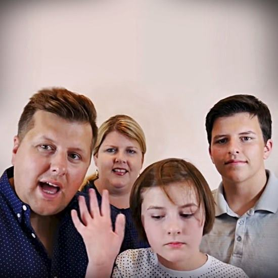 Delightful family of four with varying expressions of exasperation looking at the camera