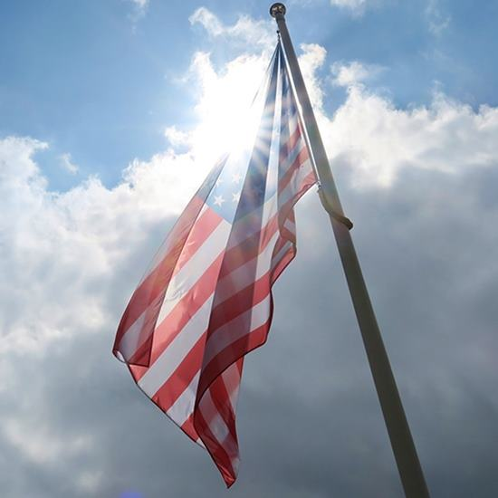 The American flag flying with the sun shining through it against a blue sky with light clouds
