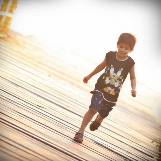 Child walking across a bridge all alone