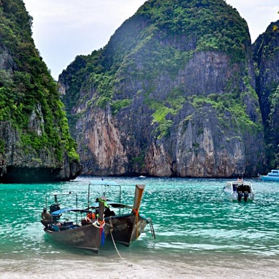Boats pulled up at a glorious beach with turquoise waters and huge rocks with trees growing on them
