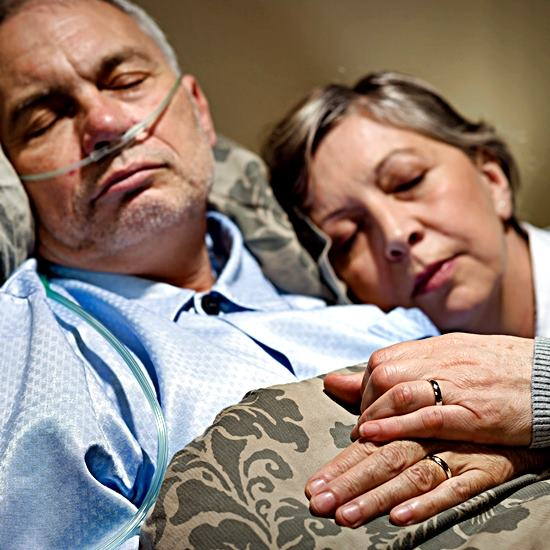 Elderly couple together - the man has a breathing tube and the woman is leaning gently on his shoulder as they clasp hands bearing wedding bands