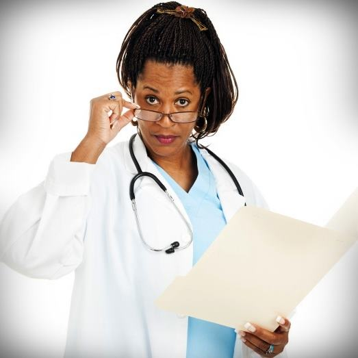 Black female doctor in a white lab coat looking skeptically over her glasses