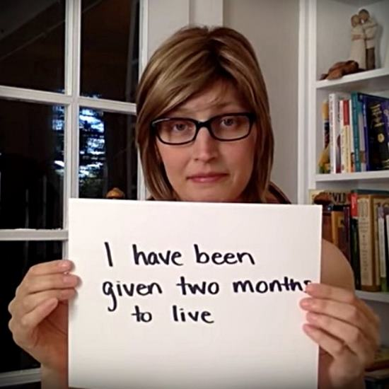 A heartbroken blonde woman with glasses holding a sign that says - I have been given two months to live