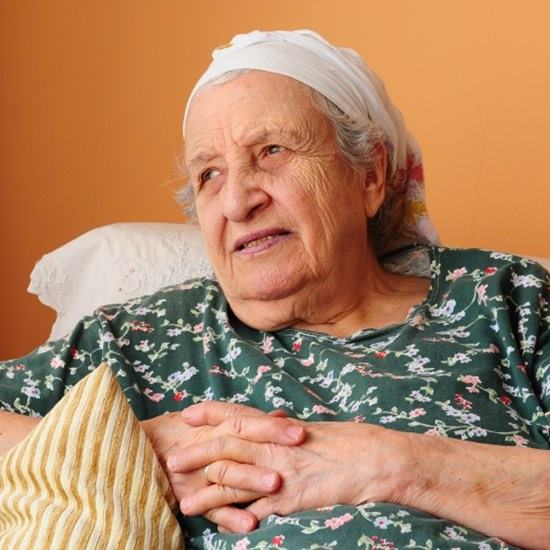Elderly woman in a green shirt leans back on a comfortable couch