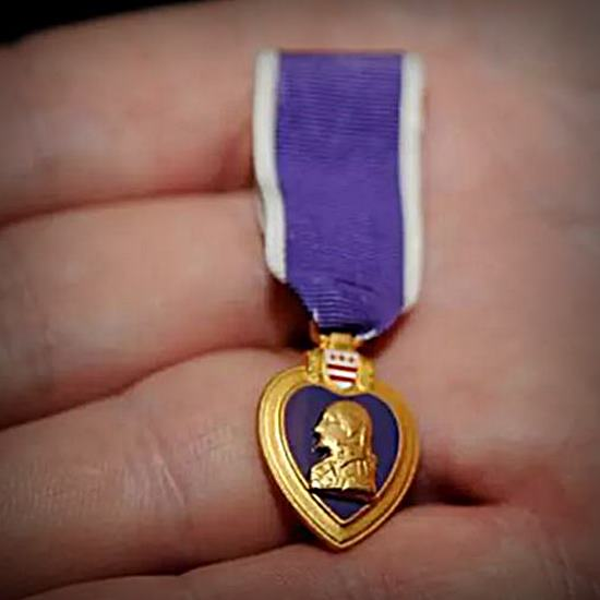 Hand holding a Purple Heart