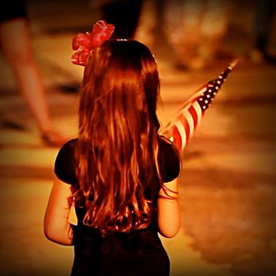little girl with long hair holding a small American flag as she waits