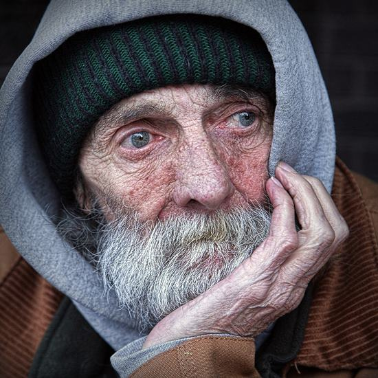Elderly man with beard in gray hoodie and warm cap
