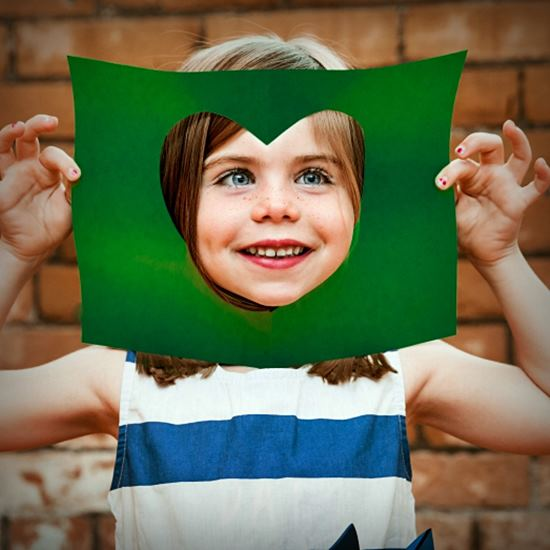 Young girl looking through a hole in green paper