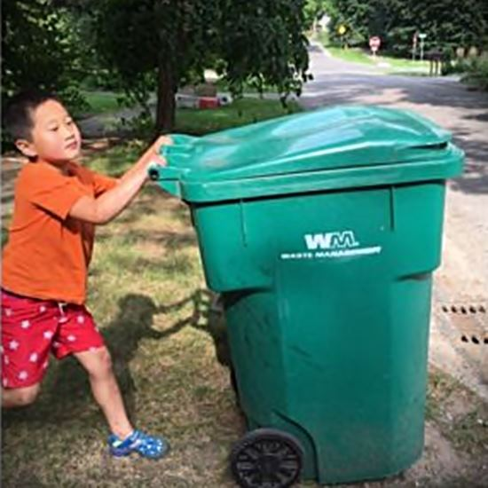 Young boy taking trash to curb