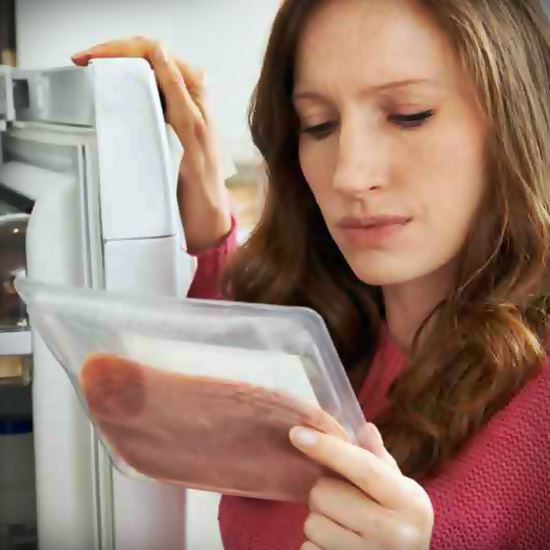 Woman looking at lunch meat package