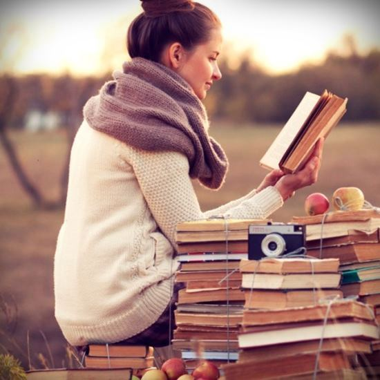 Woman with a stack of books in the field