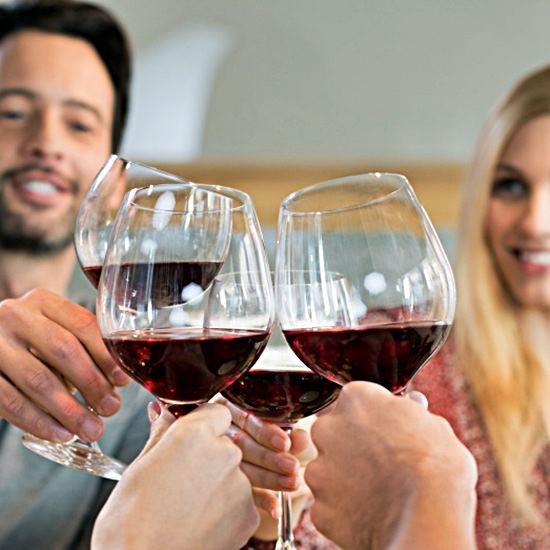 Red wine in stemmed glasses held in a toast