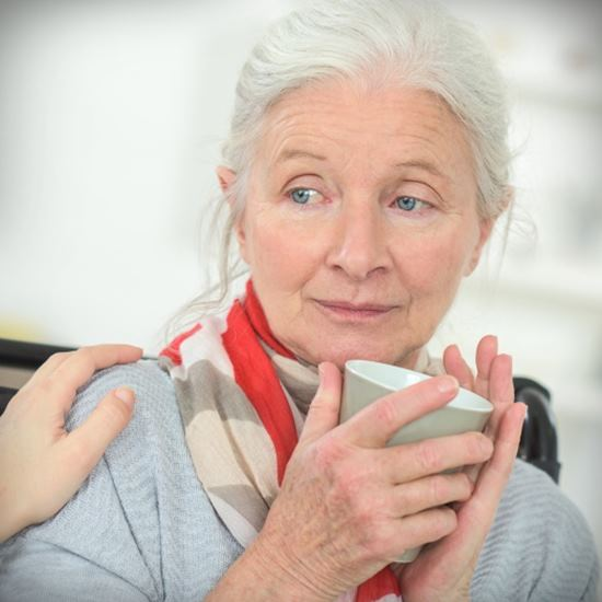 Beautiful white-haired elderly woman looking uncertain over tea