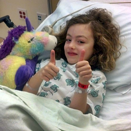 Girl in hospital bed giving thumbs up