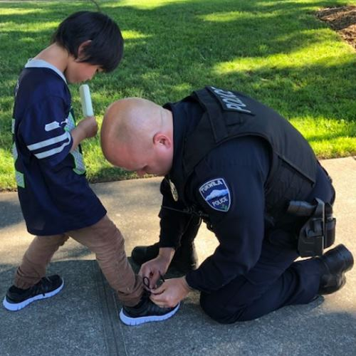 Cop kneeling to put shoes on young boy