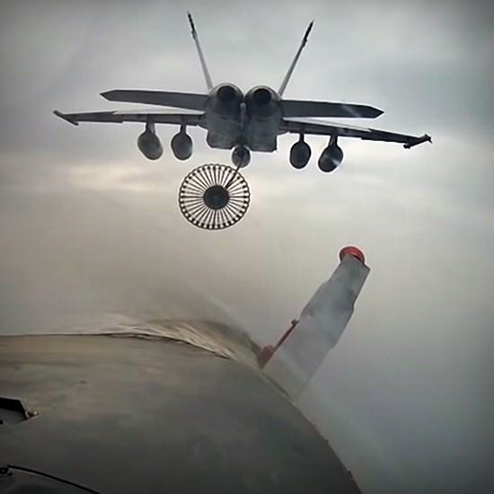 Fighter jet with parachute as seen from behind