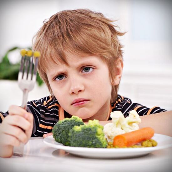 Boy with expression of disgust and a forkful of broccoli