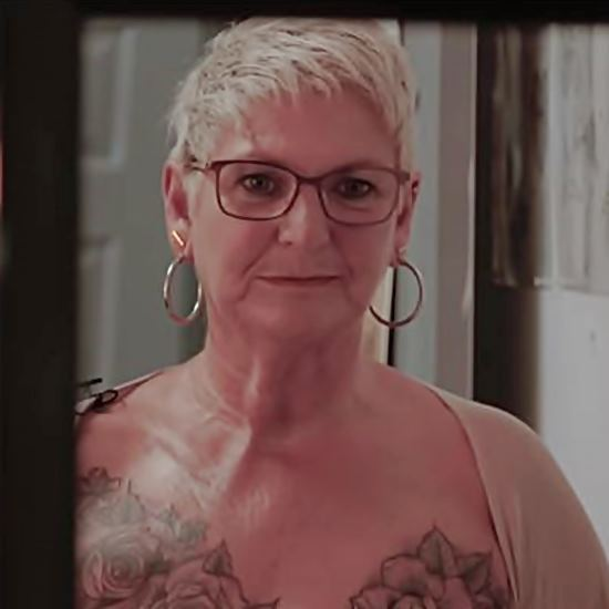 Older woman looks in mirror at new tattoo