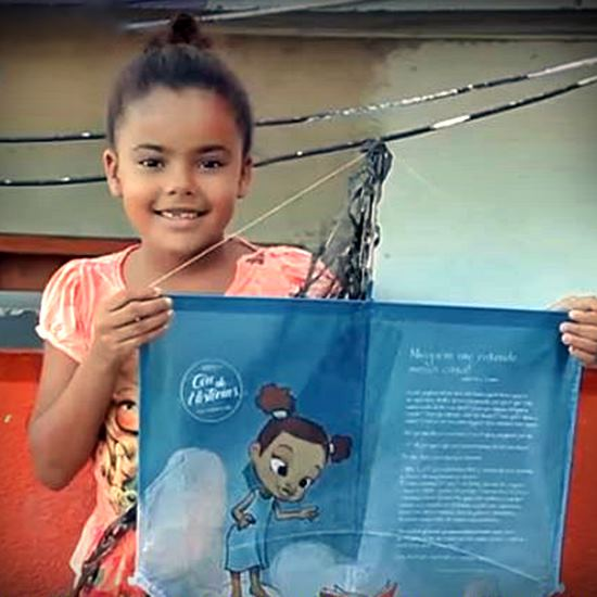 Young girl holding a kite with a story on it