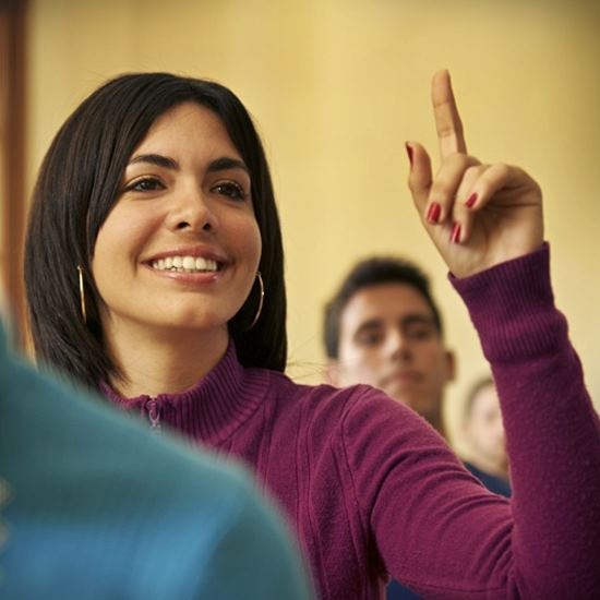 Young woman raising her hand and smiling