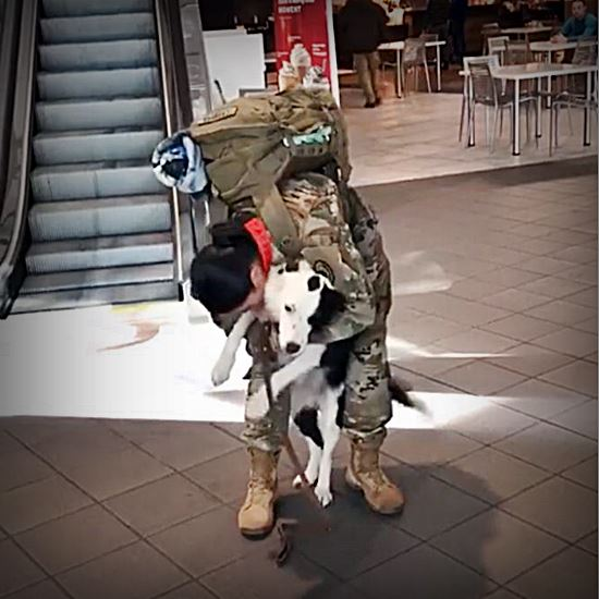 Woman soldier in full gear hugged by black and white dog at airport