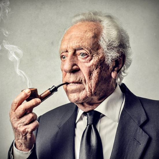 Senior man with white hair and a perplexed expression smoking a pipe