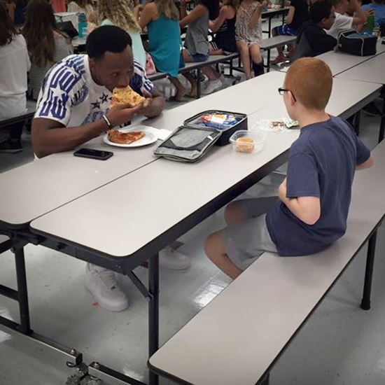boy eating with a man at a cafeteria