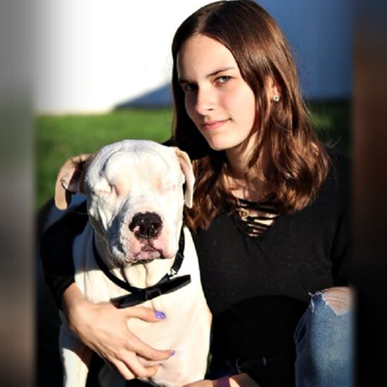 Woman with her blind white pit bull