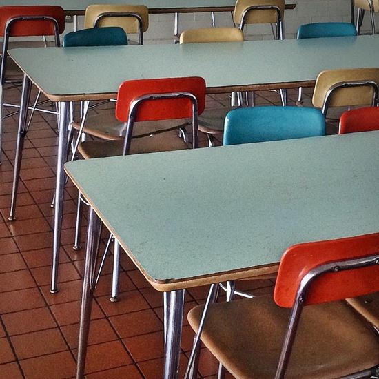 Empty school cafeteria tables and colorful chairs