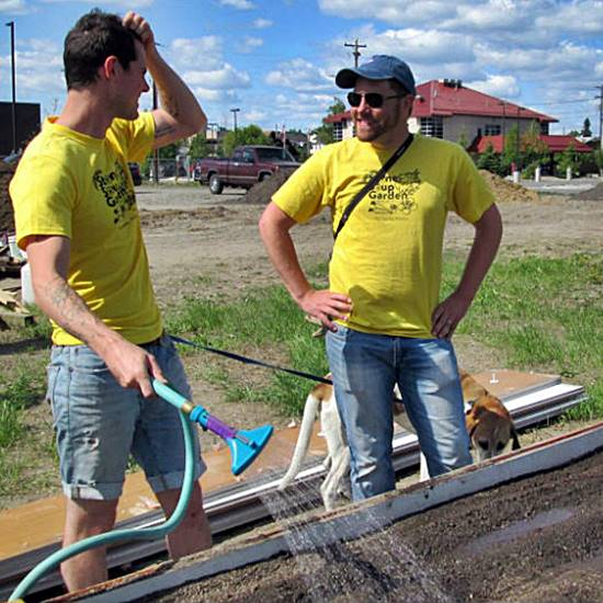 Two volunteers in yellow shirts gardening