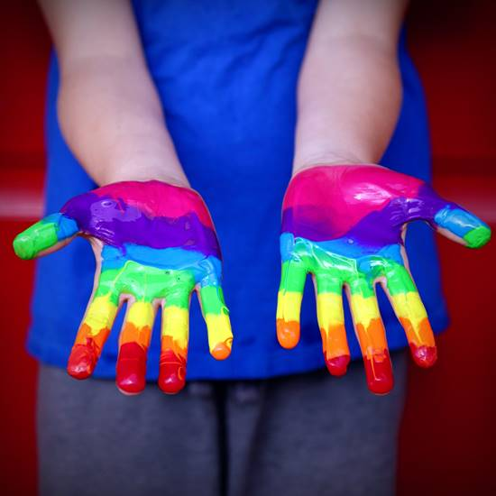 Hands dipped in rainbow paint