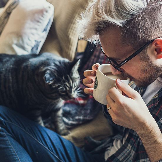 Dude on a couch with coffee and a cat - win