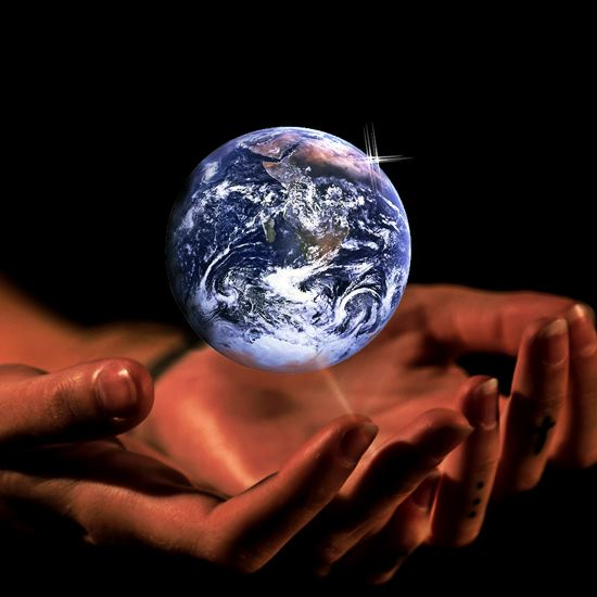 Earth globe hovering above human hands