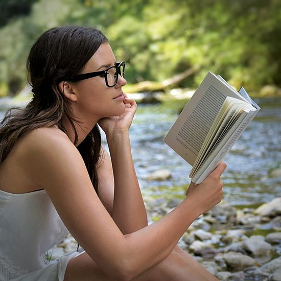 Woman in glasses reading a book by a stream