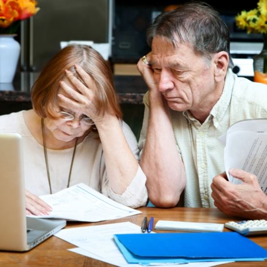 Concerned elderly couple with papers and laptop