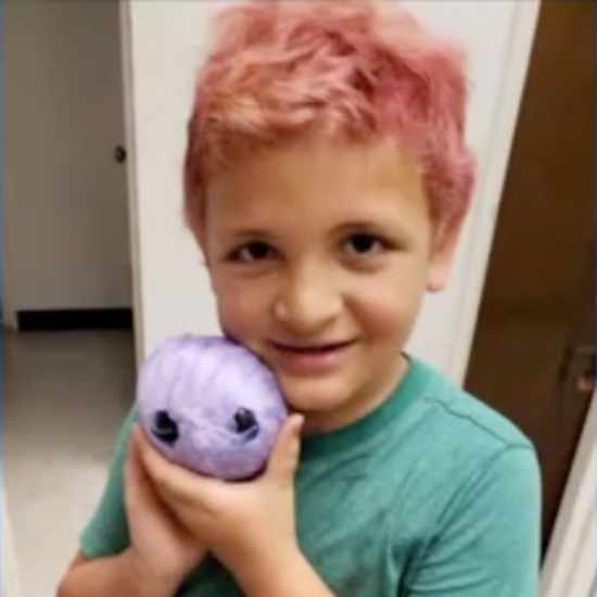 Kid with pink hair and a sweet smile