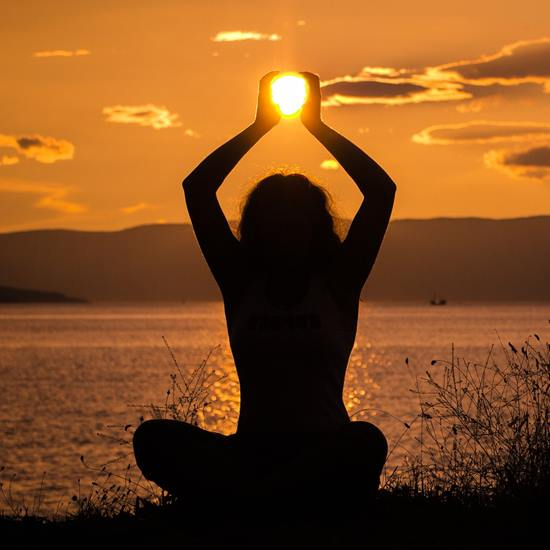 Woman sitting silhouetted in sunset holding the sun