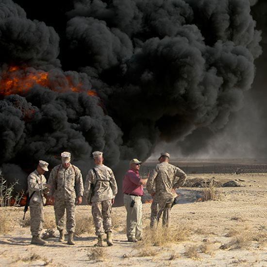 Americans in uniform in front of a massive black smoke cloud