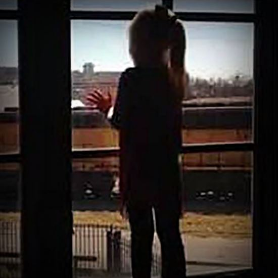 Little girl looking out the window at a passing train