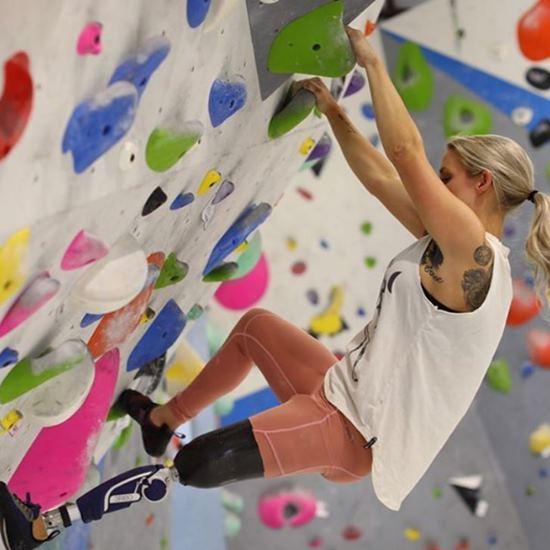 Kristie Ennis climbing a rock wall