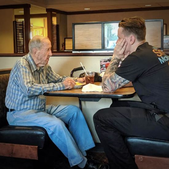 Veteran and server at a table dining