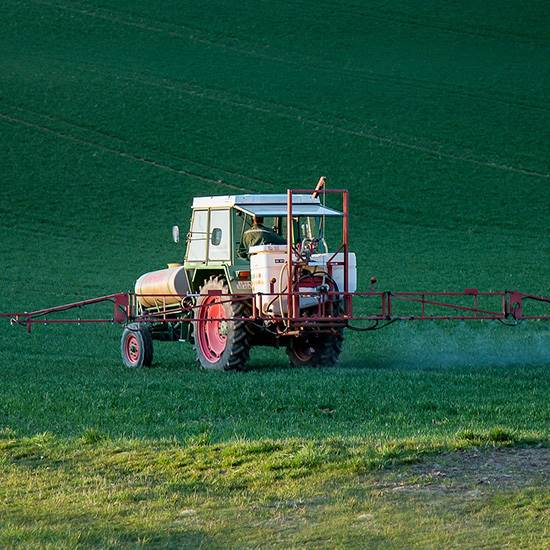Tractor with sprayer over green fields