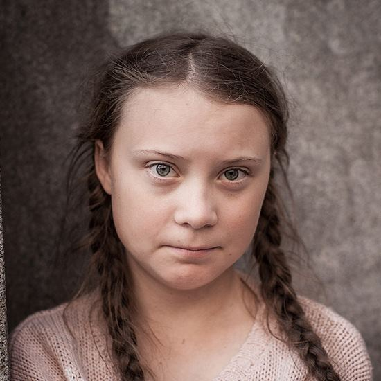 Greta Thunberg - a highly intelligent and articulate young girl in braids looking at the camera