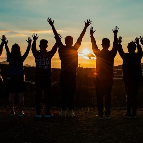 Young people raising hands in the sunset