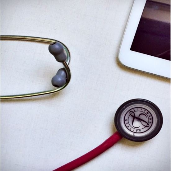 Stethoscope and tablet on a white table