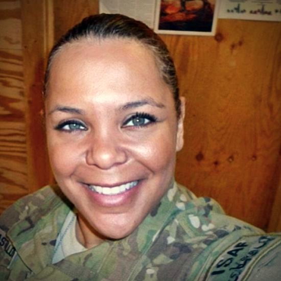 Woman in fatigues smiling