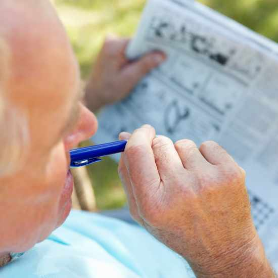 Elderly man with a pen and newspaper
