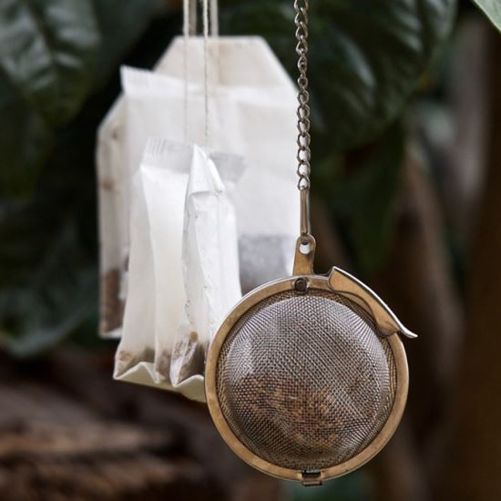 Tea bags and a tea strainer full of leaves