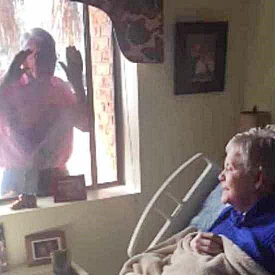 Elderly man serenading woman through the window