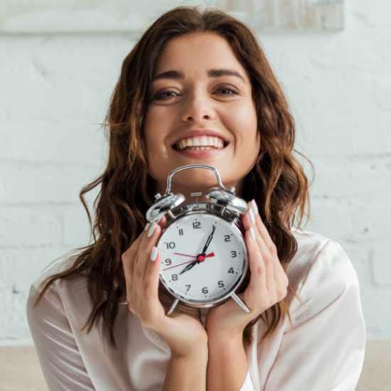Woman holding old-school alarm clock